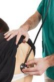 Auscultazione medica posteriore con la fine dello stetoscopio su caucasico Immagini Stock