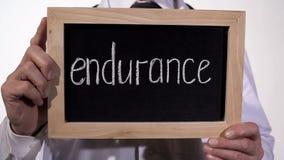 Ausdauer geschrieben auf Tafel in Doktorhände, Hoffnung für Wiederaufnahme, Stärke stockfotografie