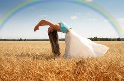 Ausdehnen der Frau in der Wiese mit Regenbogen Stockfotografie