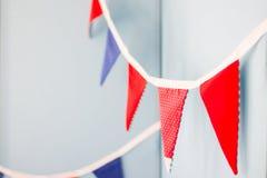 Ausdehnen von den Flaggen, die an einem blauen Hintergrund hängen Lizenzfreie Stockfotografie