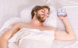 Ausdehnung nach morgens aufwachen Schließen Sie oben von den Füßen in einem Bett unter weißer Decke Mann auf dem Bett lizenzfreie stockfotografie