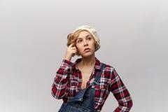 Ausdrucksvolle durchdachte junge blonde Frau in der stilvollen Retro- Kleidung schaut oben und zur Seite, die an seine Gefühle de Lizenzfreie Stockfotografie