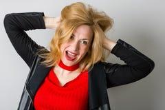 Ausdrucksvolle Frau in einer schwarzen Jacke gegen eine Wand lizenzfreies stockbild