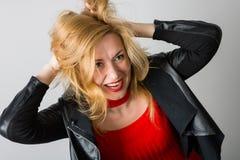 Ausdrucksvolle Frau in einer schwarzen Jacke gegen eine Wand lizenzfreies stockfoto