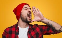 Ausdrucksvoller Hippie, der laut Nachrichten ankündigt lizenzfreies stockbild