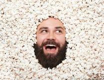 Ausdrucksvoller Mann, der im Popcorn aufwirft Lizenzfreies Stockfoto
