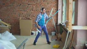 Ausdrucksvoller netter Mann in einem karierten Hemd führt Reparaturen, Spiele eine eingebildete Gitarre durch stock video