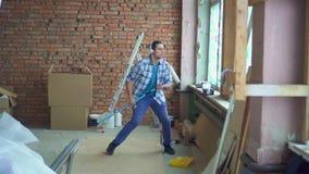 Ausdrucksvoller netter Mann im Hemd und in den Kopfhörern singt und tanzt während der Reparaturen stock video