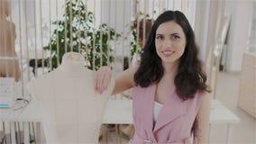 Ausdrucksvoller und reizend Modedesigner, der die Kamera bei der Stellung in ihrem modernen nähenden Büro oder in Atelier untersu stock footage