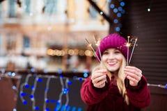 Ausdrucksvolles blondes Mädchen, das glühende Bengal-Lichter beim Chri hält Stockfotografie