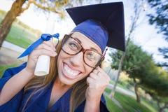 Ausdrucksvolles jugendlich graduiertes haltenes Diplom in der Kappe und im Kleid Stockfotografie