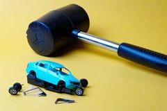 Auseinander fallend Spielzeugauto auf einem gelben Hintergrund, fielen die Räder weg vom Glas, ist als nächstes ein großer Gummih stockfoto