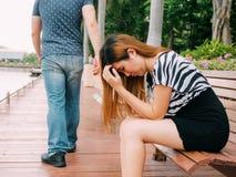 Auseinanderbrechen eines Paares mit trauriger Freundin und dem Freund, die weg mit Stadt im Hintergrund geht stockfotografie