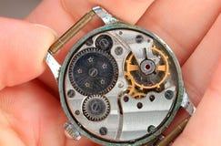 Auseinandergebaute Uhrgänge sind in der Hand des Meisters Stockfoto