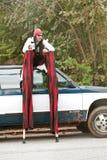 Ausführender auf Stelzen sitzt oben auf Auto Stockbild