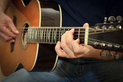 Ausführender, der auf der Akustikgitarre spielt Lizenzfreie Stockbilder