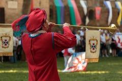 Ausführender gekleidet im Rot mit langer Trompete während der Prozession stockbild