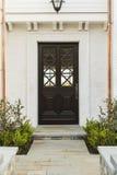 Ausführliche hölzerne Haustür des weißen Ziegelsteinhauses Stockfoto