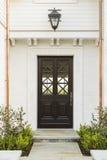 Ausführliche hölzerne Haustür des weißen Ziegelsteinhauses Lizenzfreies Stockfoto