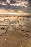 Ausführlicher sandiger Strand mit darl Wolken oben lizenzfreie stockbilder