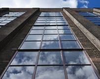 Ausführliches Bild von großen und langen Fenstern auf der Backsteinmauer in der Fabrik mit Wolken und Himmel Stockfotografie