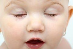 Ausführliches Gesicht des schönen Babys mit geschlossenem e Stockbild
