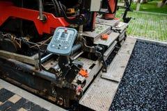 Ausführung von Reparaturarbeiten: asphaltieren Sie die Rolle, die heiße Lage des Asphalts stapelt und drückt Maschine, die Straße stockbild