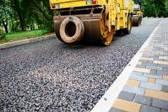 Ausführung von Reparaturarbeiten: asphaltieren Sie die Rolle, die heiße Lage des Asphalts stapelt und drückt Maschine, die Straße stockfotografie