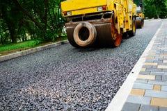 Ausführung von Reparaturarbeiten: asphaltieren Sie die Rolle, die heiße Lage des Asphalts stapelt und drückt Maschine, die Straße lizenzfreie stockbilder