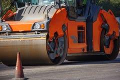 Ausführung von Reparaturarbeiten: asphaltieren Sie die Rolle, die heiße Lage des Asphalts stapelt und drückt Maschine, die Straße lizenzfreies stockfoto