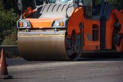 Ausführung von Reparaturarbeiten: asphaltieren Sie die Rolle, die heiße Lage des Asphalts stapelt und drückt Maschine, die Straße stockfoto