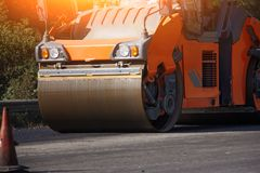 Ausführung von Reparaturarbeiten: asphaltieren Sie die Rolle, die heiße Lage des Asphalts stapelt und drückt Maschine, die Straße lizenzfreie stockfotografie