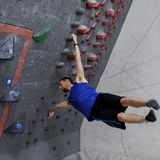 Ausführungsfahnenmast des Kletterers auf bouldering Wand stockfoto