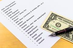 Ausgaben und Budget-Liste mit dem hölzernen Hintergrund Lizenzfreie Stockfotos