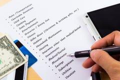Ausgaben und Budget-Liste mit dem hölzernen Hintergrund Lizenzfreie Stockbilder