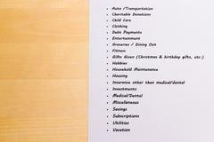 Ausgaben und Budget-Liste mit hölzernem Hintergrund Lizenzfreie Stockfotografie