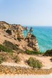 AusgabenSommerferien in der Meerblickansicht über Felsenklippen mit Meeren höhlen auf sandigem Strand aus Junge Erwachsene lizenzfreies stockbild