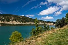 AusgabenSommerferien, die in der szenischen bunten Landschaft mit Türkissee und blauem Himmel wandern Stockfoto