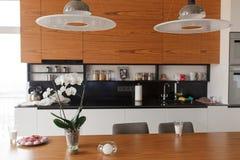 Ausgangsinnenraum mit Großraumküche, Aufenthaltsraum und Speiseraum Moderne Lichter und Holztisch lizenzfreies stockbild