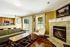 Ausgangsinnenraum mit Senfwänden und grüner Couch Stockfotografie