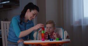 Ausgeben der Familienzeitmutter mit Baby und Entwickeln von Feinmotorik unter Verwendung der Spiele stock video
