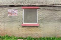 Ausgebesserte grüne gemalte alte Backsteinmauer mit dem Fenster zentriert Stockfotos