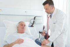 Ausgebildete medizinische Arbeitskraft, die Patientendruck überprüft lizenzfreies stockbild