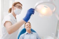 Ausgebildeter ausgezeichneter Zahnarzt, der das Licht gründet Lizenzfreie Stockfotos