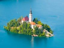 Ausgebluteter See mit Insel und Kirche Stockbilder