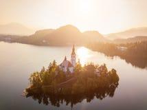 Ausgebluteter See mit Pilgerfahrt-Kirche der Annahme von Maria bei Sonnenaufgang Schattenbild des kauernden Geschäftsmannes lizenzfreies stockbild