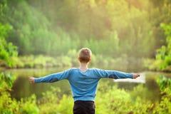 Ausgebreitete Hände des Jungen öffnen weit sich auf Naturhintergrund Stockbild