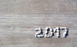 2017 ausgebreitete Steine auf einem hölzernen Pier des Hintergrundes Stockfotos