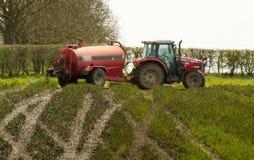 Ausgebreiteter ausgebreiteter Schlamm des roten Traktors auf Feldern stockfotos