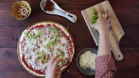 Ausgebreiteter Mozzarellakäse auf einer Pizza stock footage